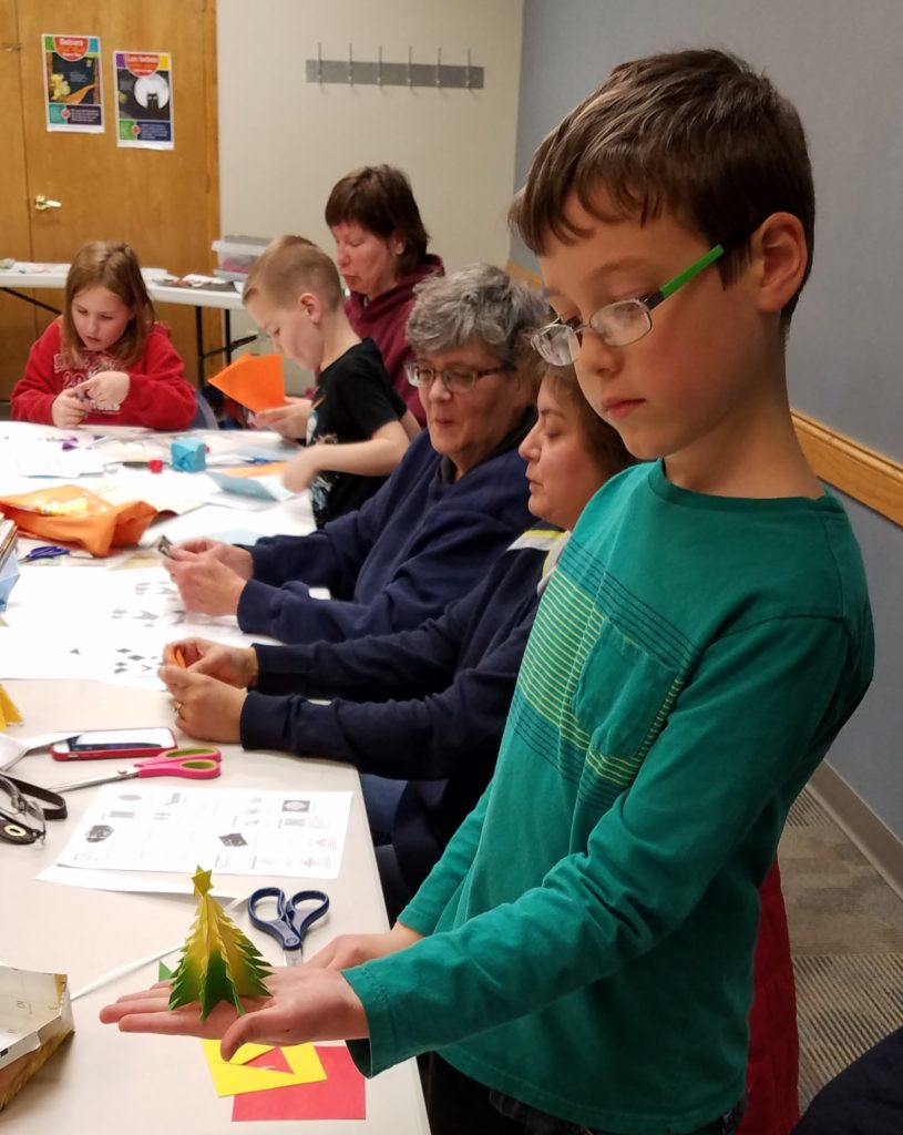 Children creating origami at Gloria's workshop